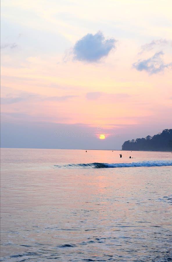 Multicolor niebo z odcieniami rewolucjonistka, błękit i kolor żółty z położenia słońcem przy horyzontem nad ocean wodą, obraz royalty free