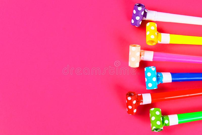 Multicolor party blowers on pink background. Multicolored party whistles. Decor for a birthday. Multicolor party blowers on pink background. Multicolored party royalty free stock images