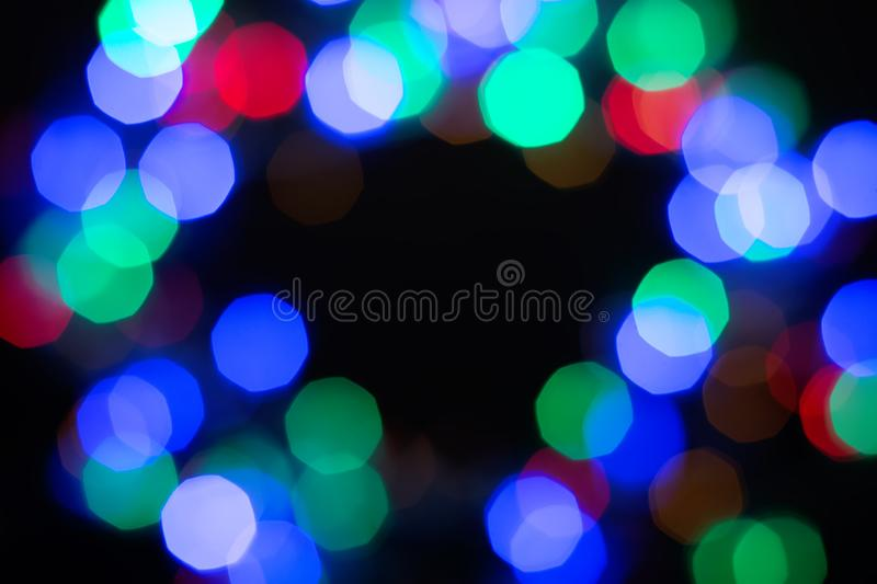 Multicolor shiny bokeh frame on black background. Abstract black, green, purple, red and blue glitter royalty free stock photography