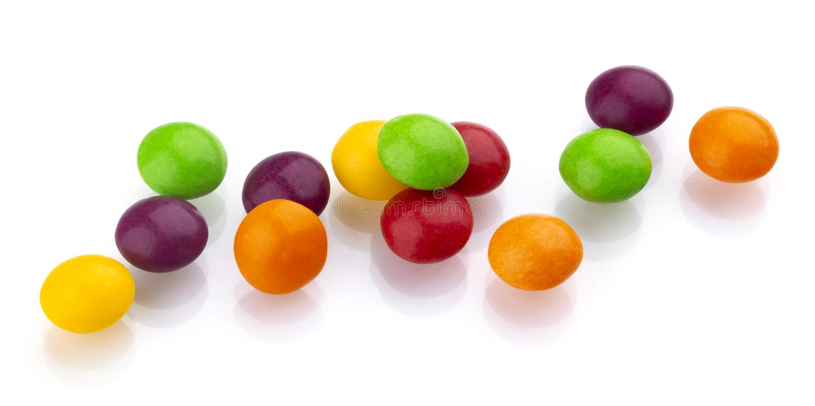 Multicolor shiny nuts and raisins dragee isolated on white background royalty free stock photography