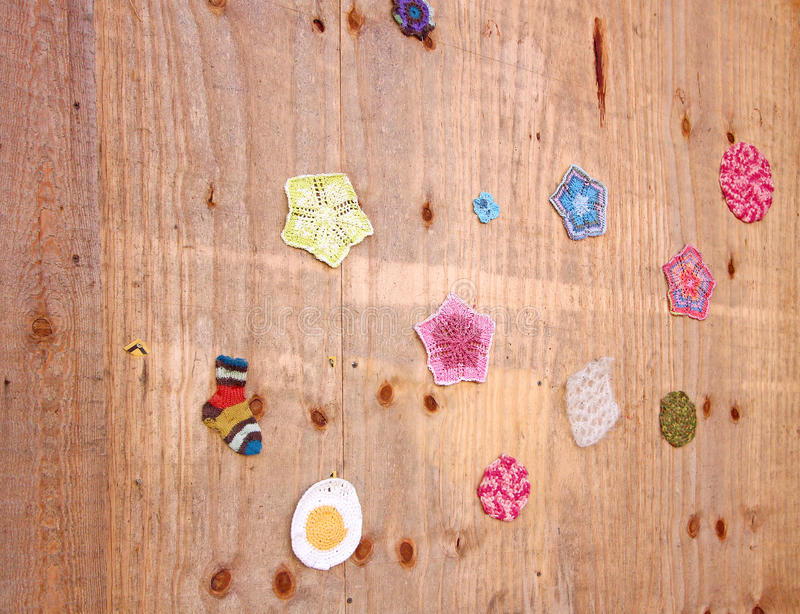 Multicolor small crocheted things on wooden wall royalty free stock images
