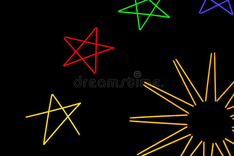 Multicolor star shaped neon windmill in dark night royalty free stock photo