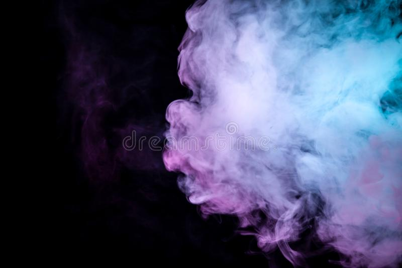 Multicolor, thick smoke, illuminated by colored in blue, purple and pink light against a dark black isolated background, welded royalty free stock photo