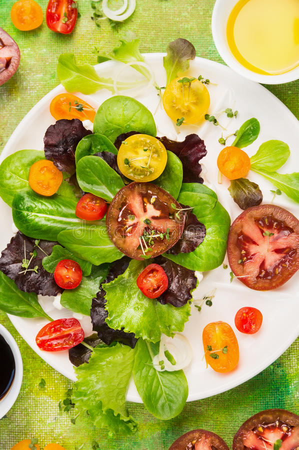Multicolor Tomatoes various salad in white plate with greens, oil and balsamic vinegar, top view royalty free stock photography
