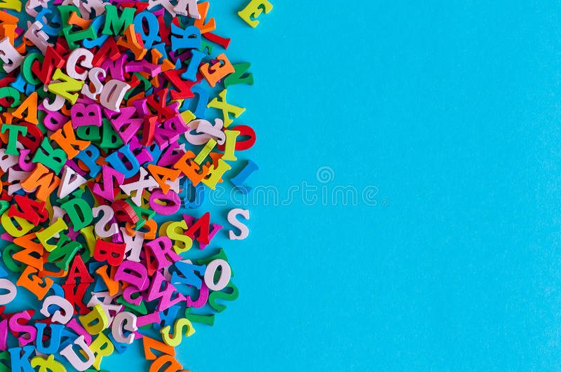 Multicolored Alphabet letters of the English alphabet are lined on blue background with empty space. Education or royalty free stock photography