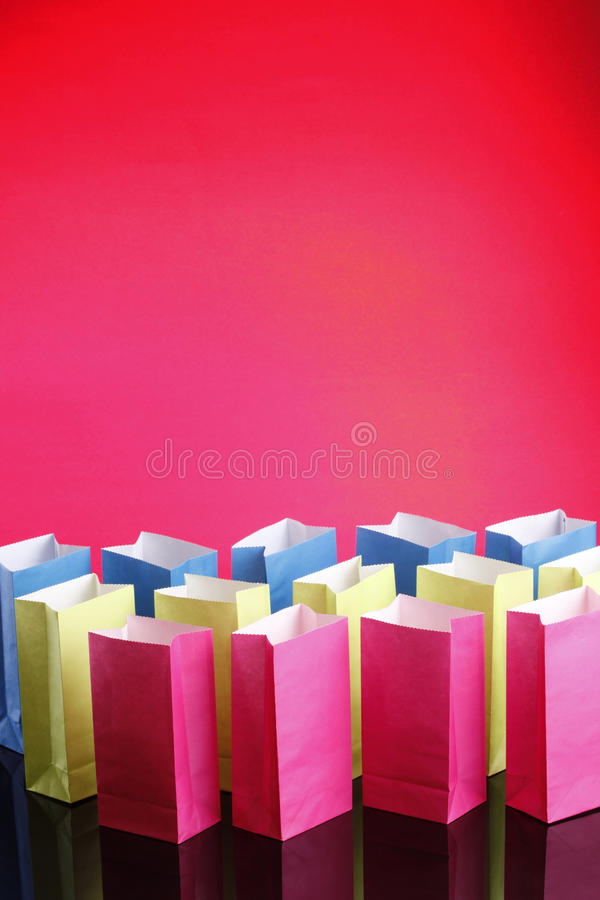 Multicolored bags on red. Recyclable Paper bags on Blue light stock images