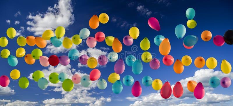 Multicolored ballons stijgen in de hemel Tegen de blauwe hemel met witte wolken royalty-vrije stock afbeeldingen