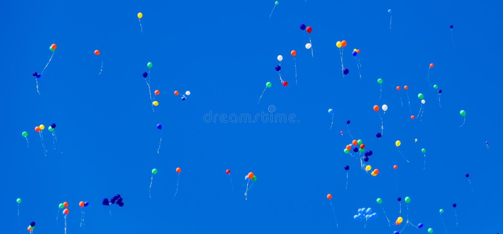Multicolored balls, filled with helium, fly in the blue sky.  stock image