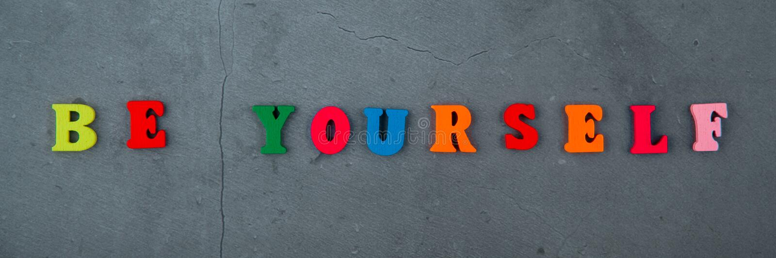 The multicolored be yourself word is made of wooden letters on a grey plastered wall background.  stock image