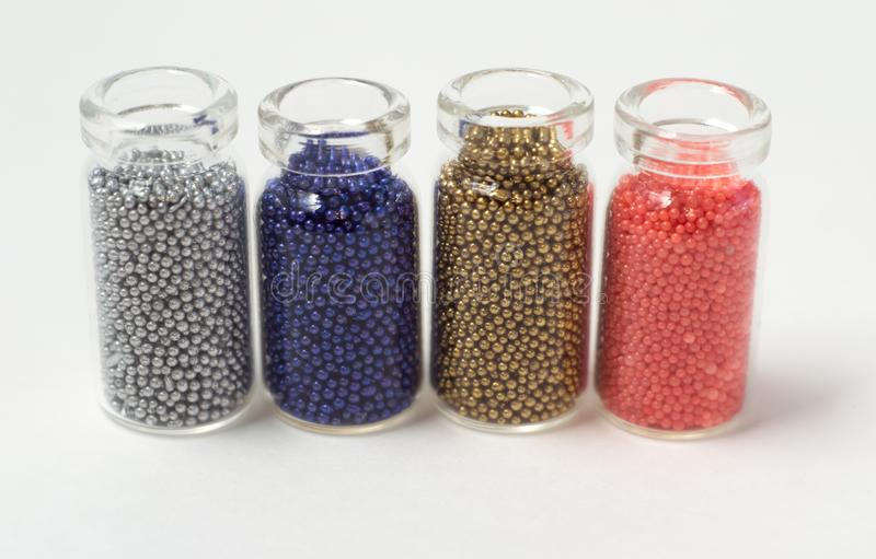 Multicolored beads in glass jars. Beads are poured on a white background. Plastic multi-colored polymers. Plastic pillets.  royalty free stock images