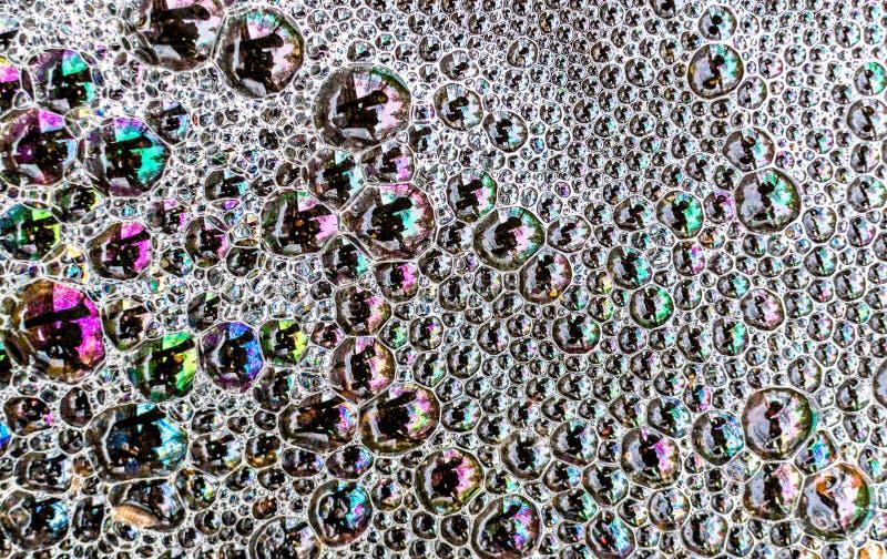 Multicolored bellen van het zeepschuim op de oppervlakte van een vulklei van water leiden tot stock foto