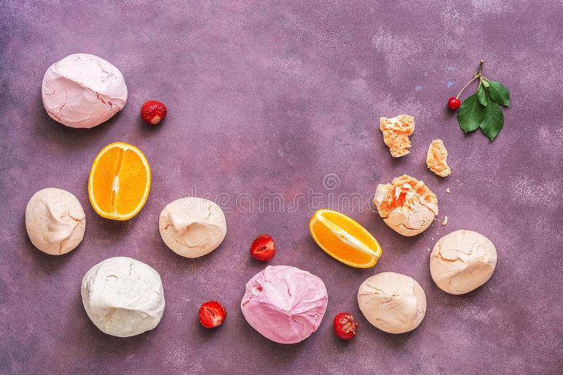 Multicolored berry meringues on a beautiful abstract purple background. Top view, copy space. stock photography