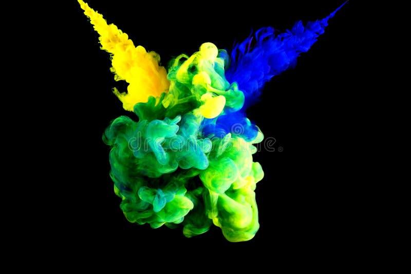 Multicolored botsing van verf, het mengen zich van blauwe en gele kleuren in het water tegen stock foto's