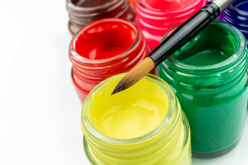 Multicolored bottles poster color and paintbrush  on a white background Isolated Paints in containers. Multicolored bottles poster color and paintbrush  on a royalty free stock images