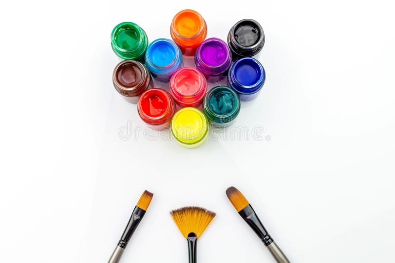 Multicolored bottles poster color and paintbrush  on a white background Isolated Paints in containers . Multicolored bottles poster color and paintbrush  on a royalty free stock photo