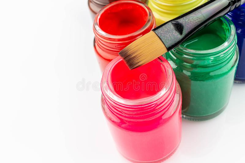 Multicolored bottles poster color and paintbrush on a white background Isolated Paints in containers . Multicolored bottles poster color and paintbrush  on a stock image
