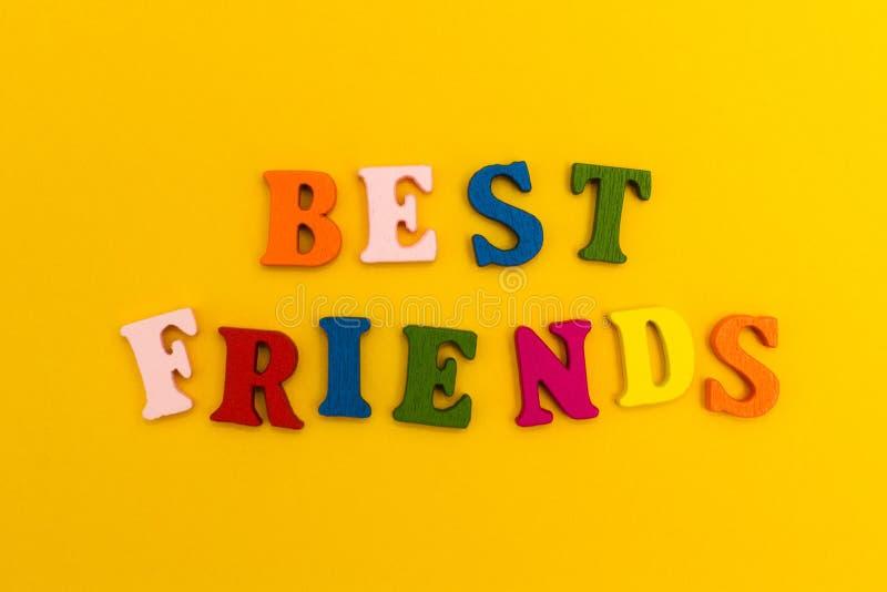Multicolored brieven op een gele achtergrond Beste Vrienden stock fotografie