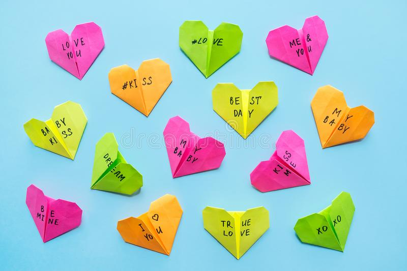 Multicolored bright paper origami hearts with text Love You, kiss, baby, be mine. Many pink, orange, yellow, green, origami paper royalty free stock image