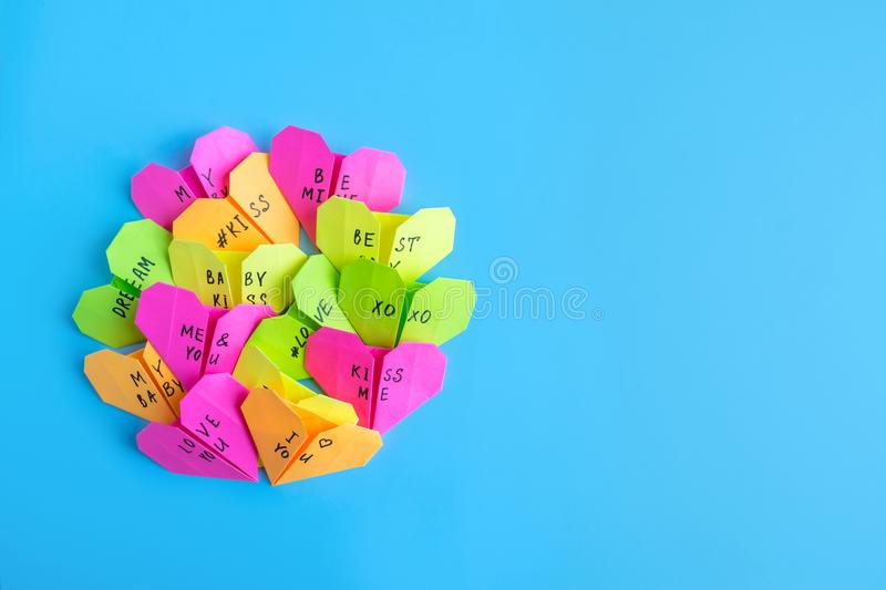 Multicolored bright paper origami hearts with text Love You, kiss, baby, be mine. Many pink, orange, yellow, green, origami paper stock photo