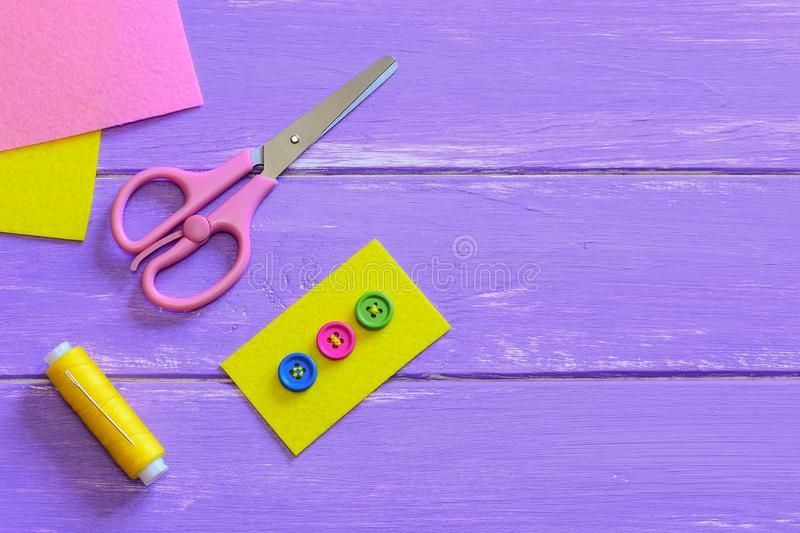Multicolored buttons sewn to the yellow felt piece. Scissors, thread, felt pieces on a wooden background with copy space for text. Sewing basics. How to sew a royalty free stock photo