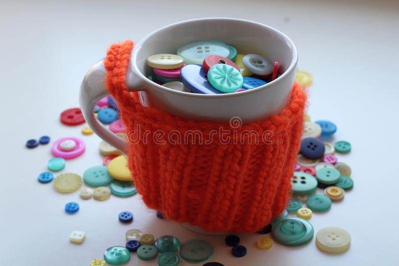 Multicolored buttons in a white cup wrapped in a knitted and warm orange case stock photo