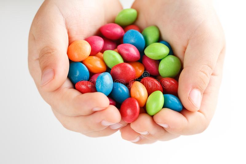 Multicolored candies in the hands of a child on a white isolated background. Rainbow colors in round drops, bright colors and an explosion of taste. View from stock photo