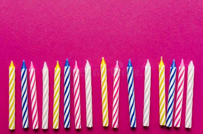 Multicolored candles for cake on paper background royalty free stock image