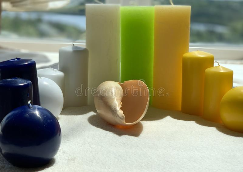 Colorful candles, small and large, seashell stock images