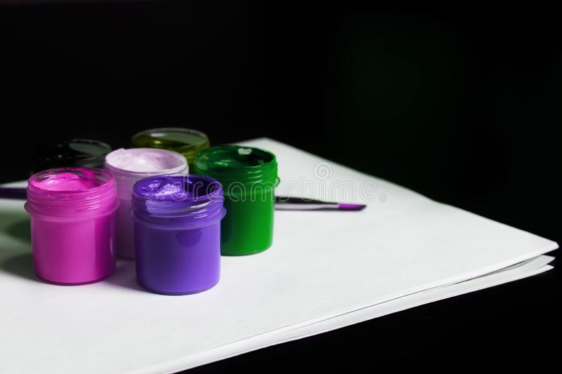 Multicolored cans of gouache with Paintbrush stock photos