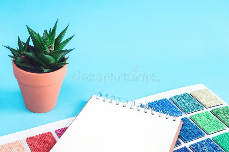 Multicolored carpet swatches book and notepad on blue royalty free stock image