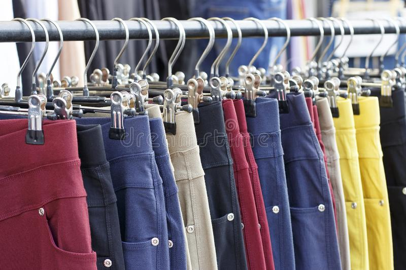 Multicolored casual pants hanging on hanger close up, side view. Multicolored casual pants hanging on a hanger close up, side view stock image
