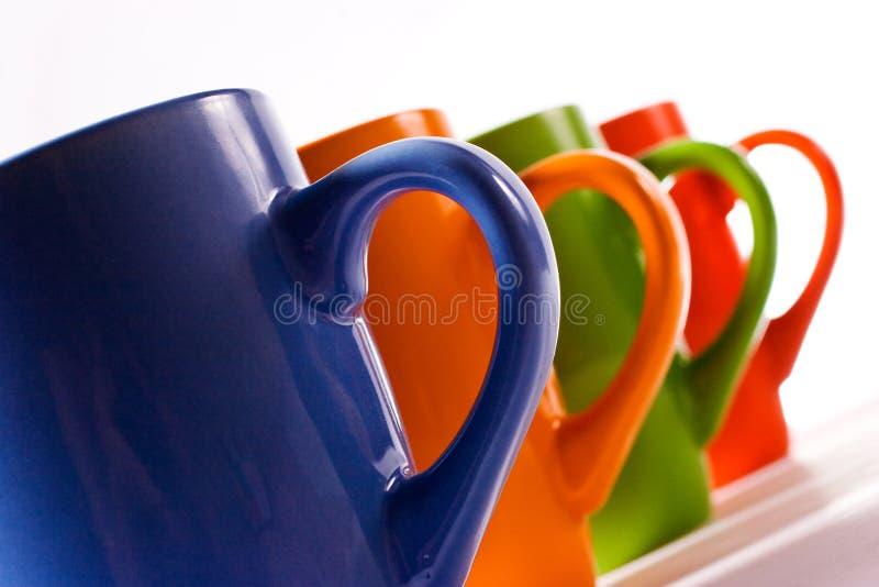 Multicolored ceramische mokken over wit royalty-vrije stock foto's