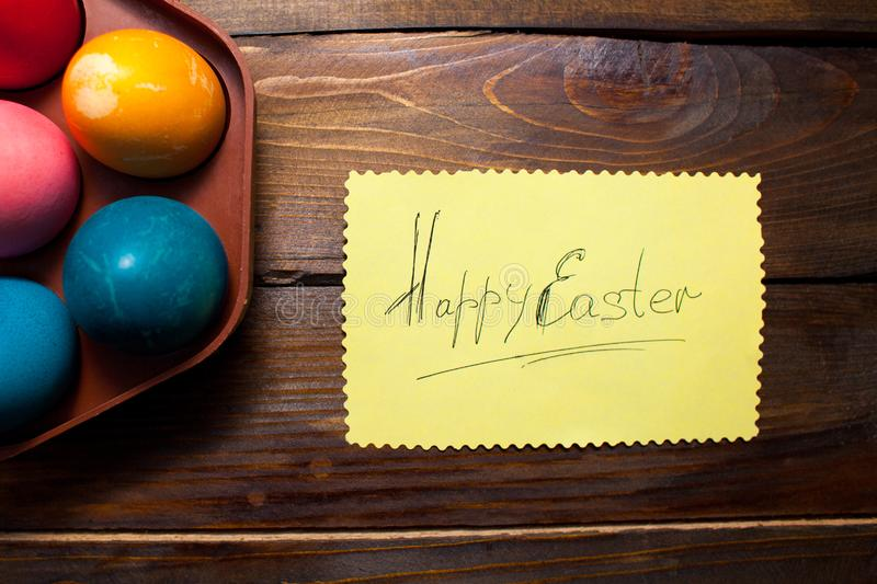 Multicolored chicken, painted eggs for the Easter holiday in box and leaf with the inscription Happy Easter on wooden weathering b royalty free stock photos