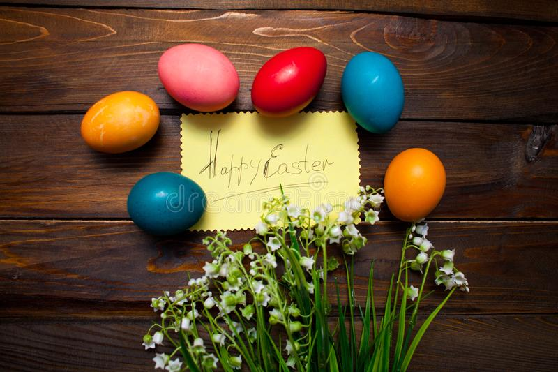 Multicolored chicken, painted eggs for the Easter holiday with lilies of the valley and leaf with the inscription Happy Easter on. Wooden weathering background royalty free stock photography