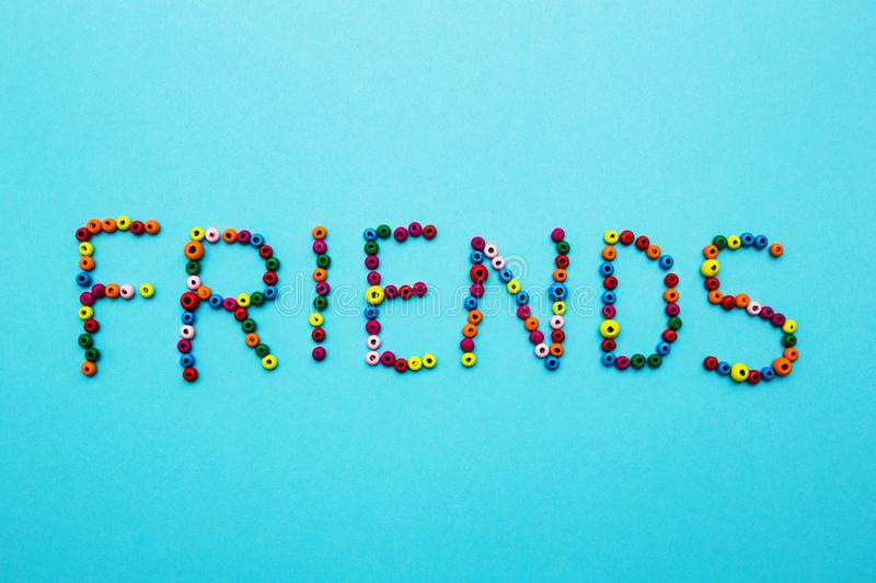 Multicolored children`s beads, scattered on a blue background, the word. `friends stock photo
