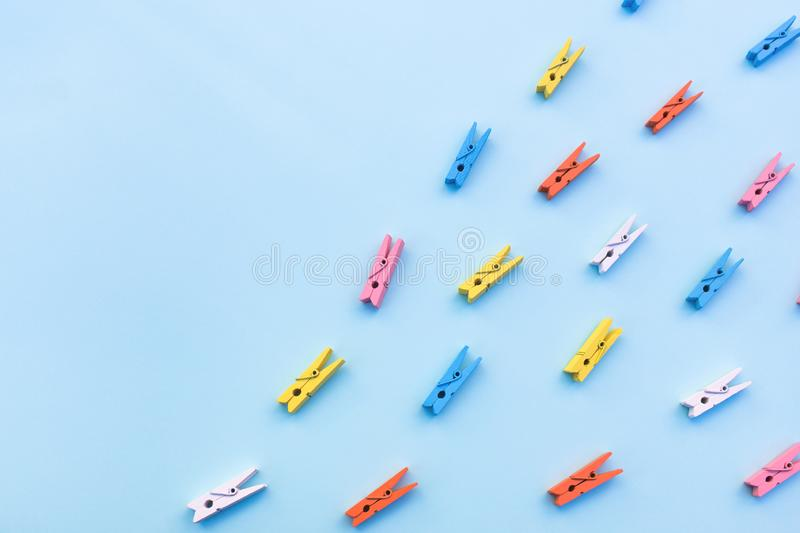 Multicolored clothespins on a blue background stock images