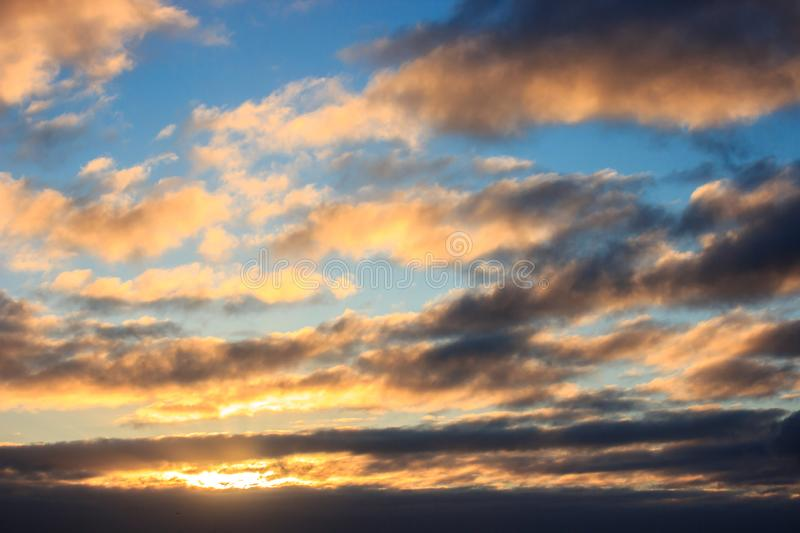 Multicolored clouds at dawn. bright sky filled with sun, the morning of a new day. active awakening of the world royalty free stock image