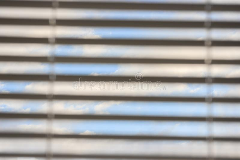 Multicolored clouds at dawn, view through the blinds. bright sky filled with sun, the morning of a new day. active awakening of royalty free stock image