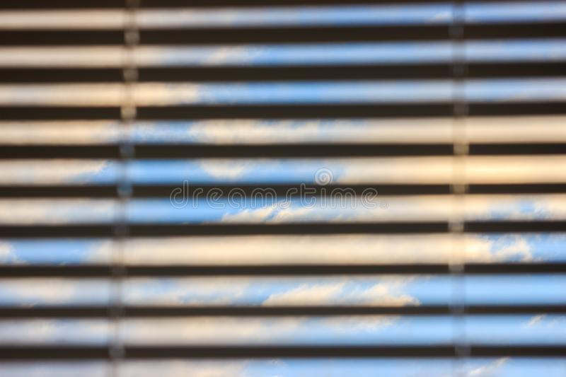 Multicolored clouds at dawn, view through the blinds. bright sky filled with sun, the morning of a new day. active awakening of royalty free stock photos