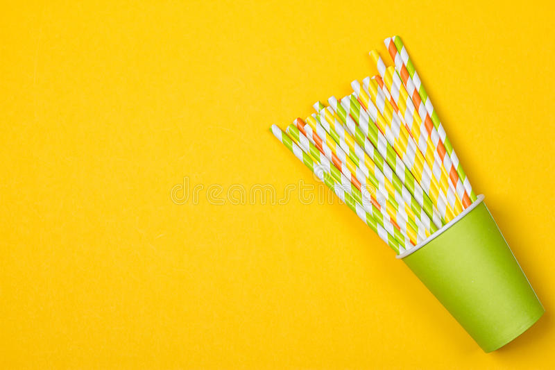 Multicolored cocktail tubes in green paper disposable cup royalty free stock photo