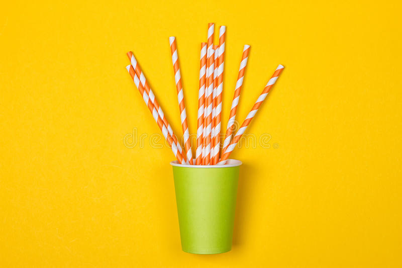 Multicolored cocktail tubes in green paper disposable cup stock photography