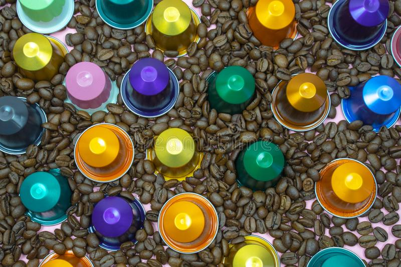 Multicolored coffee pod capsule on coffee beans close up stock photography