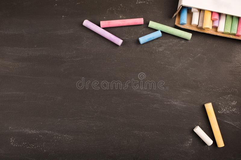 Multicolored colorful crayons lie on black chalkboard in classroom school college, copy space royalty free stock image