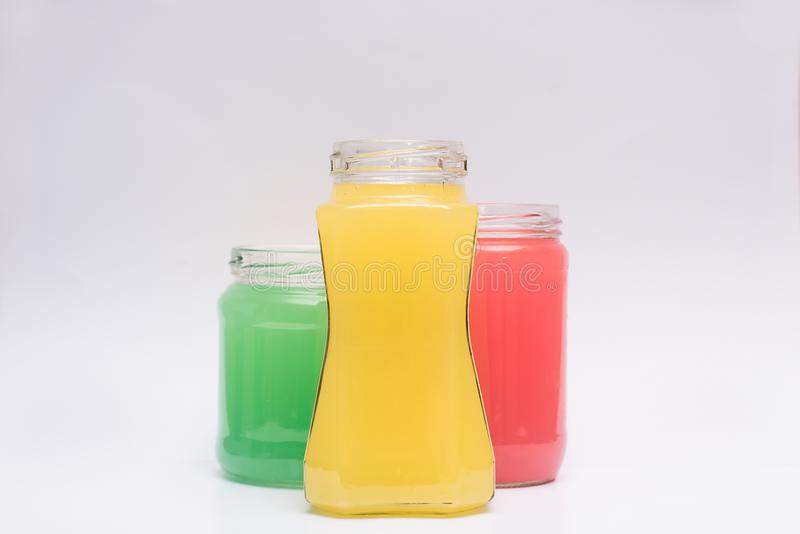 Glass containers with colored liquid. Multicolored containers of different shapes with substance on a white background stock images