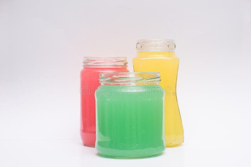 Glass containers with colored liquid. Multicolored containers of different shapes with substance on a white background stock photos