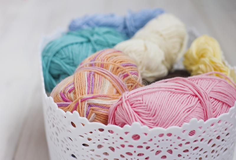 Multicolored cotton yarn in basket on white wooden background royalty free stock photos