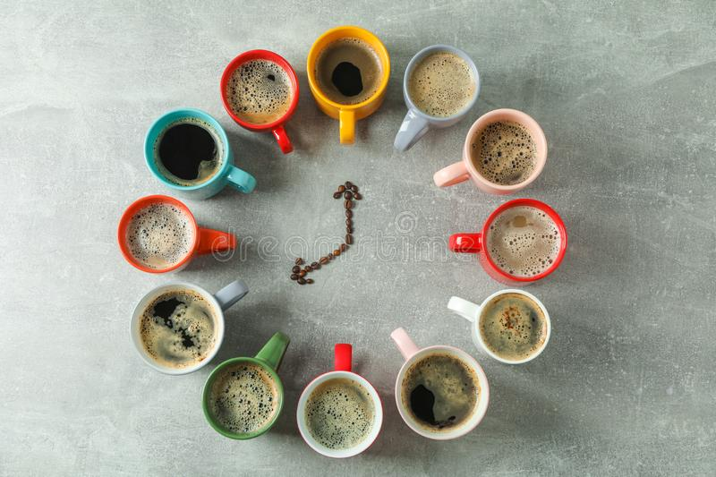 Multicolored cups of coffee and coffee beans on grey background, top view stock photography