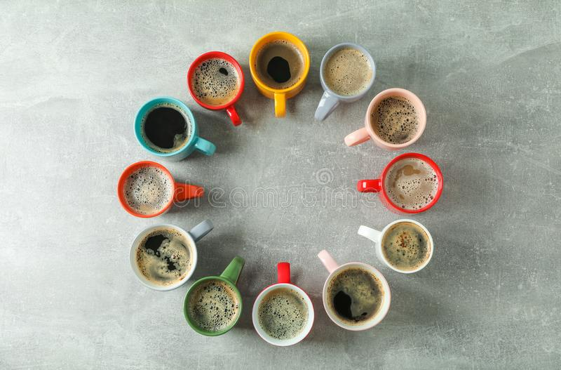 Multicolored cups of coffee circle on grey background, top view royalty free stock images