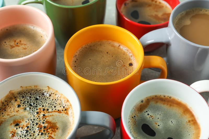 Multicolored cups of coffee on grey table as background royalty free stock photography