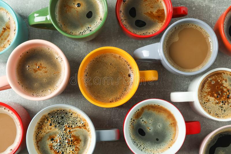 Multicolored cups of coffee on grey table as background stock photos